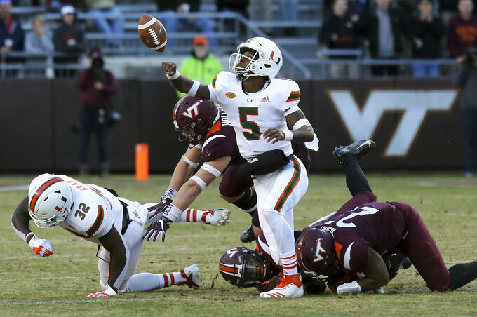 Miami quarterback N'Kosi Perry has the ball knocked from his hand but is able to recover during the first half an NCAA college football game against Virginia Tech in Blacksburg, Va., Saturday, Nov. 17 2018. (Matt Gentry/The Roanoke Times via AP)