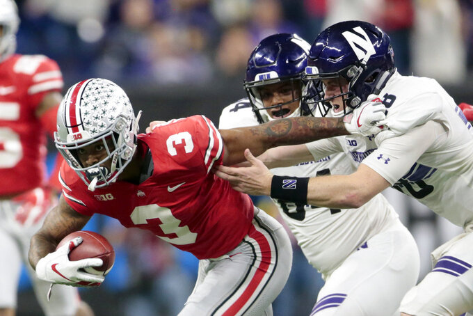 Ohio State cornerback Damon Arnette (3) runs with the ball after intercepting a pass by Northwestern quarterback Clayton Thorson, right, as Northwestern wide receiver Cameron Green, center, watches during the second half of the Big Ten championship NCAA college football game, Saturday, Dec. 1, 2018, in Indianapolis. (AP Photo/AJ Mast)