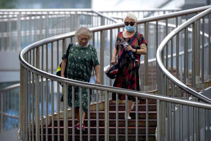 People wearing face masks to protect against COVID-19 walk down a staircase on a pedestrian bridge in Beijing, Wednesday, Aug. 4, 2021. The coronavirus's delta variant is challenging China's costly strategy of isolating cities, prompting warnings that Chinese leaders who were confident they could keep the virus out of the country need a less disruptive approach. (AP Photo/Mark Schiefelbein)