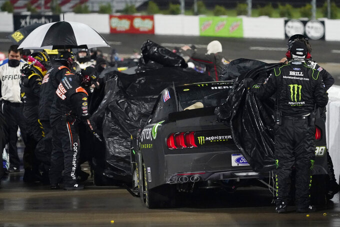 Pit crews cover cars during a rain delay in the NASCAR Xfinity Series auto race at Martinsville Speedway in Martinsville, Va., Friday, April 9, 2021. (AP Photo/Steve Helber)
