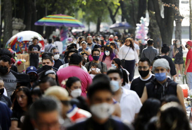 Families walk along Mexico City's Reforma Avenue during Day of the Dead celebrations, Sunday, Oct. 18, 2020. (AP Photo/Eduardo Verdugo)