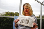 "In this Jan. 30, 2019, photo, Mechelle Boyle holds a newspaper with an iconic photo from the school shooting showing her embracing Cathi Rush as she speaks during an Associated Press interview in Parkland, Fla. ""The terror that we felt, I see it on my face every time I look at the picture,"" Boyle said. (AP Photo/Brynn Anderson)"