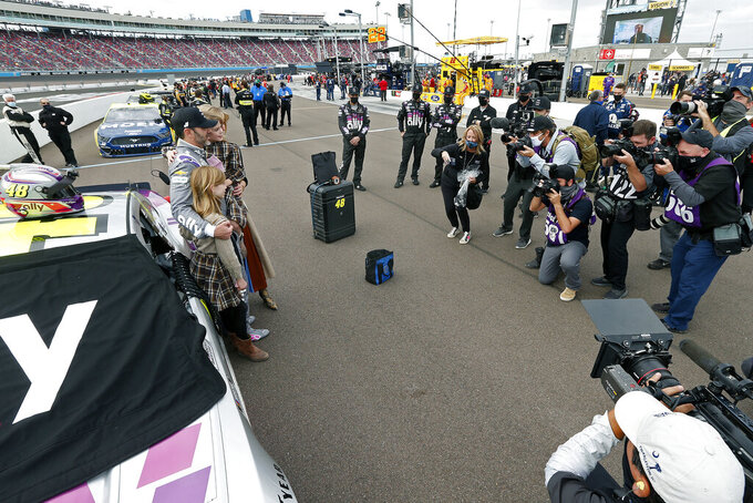 Jimmie Johnson, left, poses for photographers with his family on pit road prior to a NASCAR Cup Series auto race at Phoenix Raceway, Sunday, Nov. 8, 2020, in Avondale, Ariz. (AP Photo/Ralph Freso)