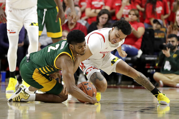George Mason guard Xavier Johnson, left, and Maryland guard Anthony Cowan Jr. compete for the ball during the second half of an NCAA college basketball game Friday, Nov. 22, 2019, in College Park, Md. Maryland won 86-63. (AP Photo/Julio Cortez)