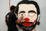 An anti-government protester and graffiti painter draws Prime Minister Saad Hariri as a clown on the wall during ongoing protests against the government, in Beirut, Lebanon, Saturday, Nov. 9, 2019. Lebanon's president is meeting with several Cabinet ministers and top banking officials in search for solutions for the deepening financial and economic crisis. (AP Photo/Bilal Hussein)