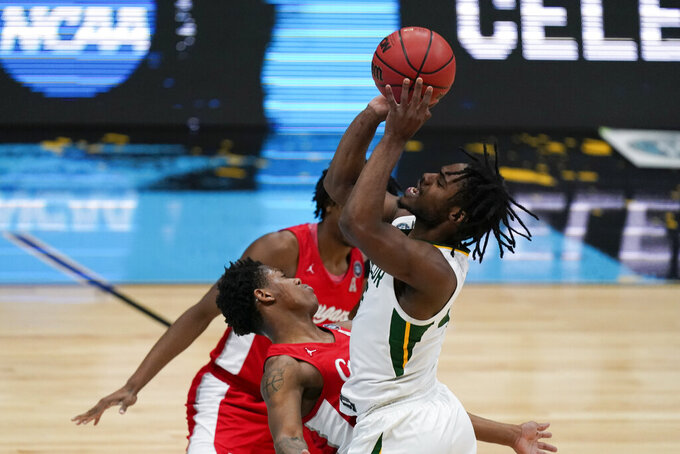Baylor guard Davion Mitchell (45) shoots over Houston guard Marcus Sasser, left, during the first half of a men's Final Four NCAA college basketball tournament semifinal game, Saturday, April 3, 2021, at Lucas Oil Stadium in Indianapolis. (AP Photo/Michael Conroy)