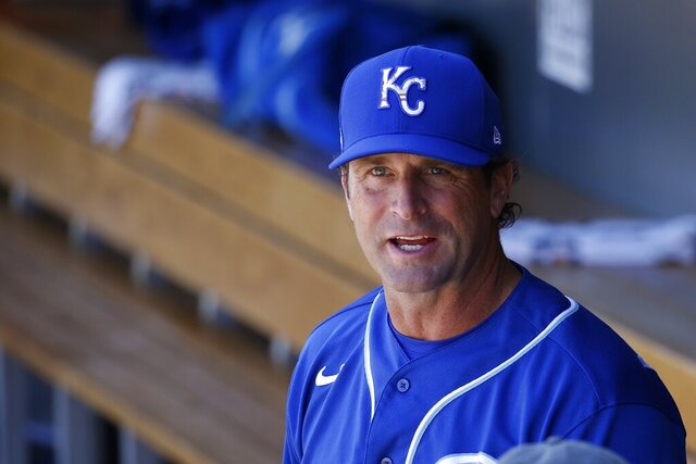 """FILE - In this March 9, 2020, file photo, Kansas City Royals manager Mike Matheny pauses in the dugout prior to a spring training baseball game against the Arizona Diamondbacks in Scottsdale, Ariz. Forget about those halcyon first few days of spring training, when arranging for the right tee time on the right golf course is often more challenging than the work on the field. When major leaguers report next week for spring training 2.0 — or perhaps more accurately, baseball's first summer camp — time will be one precious commodity with about three weeks before opening day. """"We're going to have some live batting practices the first day they show up. Day 1 and Day 2. ... Multiple ups for the starters,"""