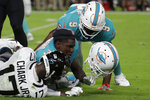Miami Dolphins corner back Chris Lammons' (30) helmet comes off as he and running back Mark Walton (9) tackle Jacksonville Jaguars wide receiver D.J. Chark (17) during the first half of an NFL football preseason game, Thursday, Aug. 22, 2019 in Miami Gardens, Fla. (AP Photo/Lynne Sladky)