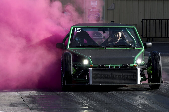 """A racer spews pink smoke from his car during a """"gender reveal"""" at Bandimere Speedway west of Denver on Wednesday, May 5, 2021. The Colorado State Patrol runs a program called """"Take it to the Track"""" in hopes of luring racers away from public areas to a safer and more controlled environment, even allowing participants to race a trooper driving a patrol car. The program's goals have gained new importance and urgency this year as illegal street racing has increased amid the coronavirus pandemic. (AP Photo/Thomas Peipert)"""