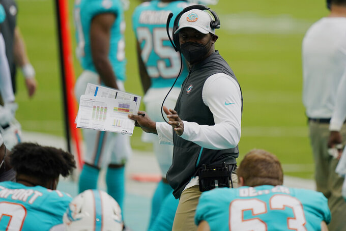 Miami Dolphins head coach Brian Flores talks to players on the sidelines during the first half of an NFL football game against the Cincinnati Bengals, Sunday, Dec. 6, 2020, in Miami Gardens, Fla. (AP Photo/Lynne Sladky)