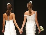 FILE -- In this Thursday, Oct. 23, 2014 file photo, models hold hands on the catwalk during a wedding fashion show with same-sex couples, dubbed