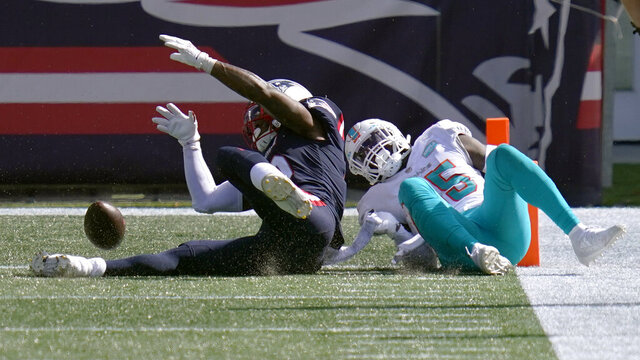 New England Patriots wide receiver N'Keal Harry, left, fumbles the ball at the goal line in front of Miami Dolphins linebacker Jerome Baker, right, in the second half of an NFL football game, Sunday, Sept. 13, 2020, in Foxborough, Mass. The ball rolled out of the end zone for a Dolphins touchback. (AP Photo/Charles Krupa)