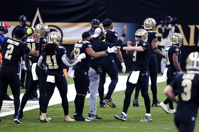 New Orleans Saints quarterback Drew Brees (9) is greeted by teammates as he returns to the bench after throwing a touchdown pass to Michael Thomas in the first half of an NFL wild-card playoff football game against the Chicago Bears in New Orleans, Sunday, Jan. 10, 2021. (AP Photo/Butch Dill)