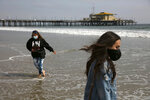 FILE - In this June 23, 2020, file photo, Malia Pena, foreground, and her mother, Lisa Torriente, wear masks as they visit the beach in Santa Monica, Calif. (AP Photo/Jae C. Hong, File)