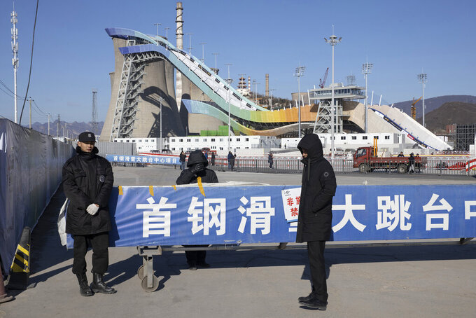 FILE - In this Dec. 11, 2019, file photo, security personnel guard an entrance to the Big Air Shougang, a venue newly built for the 2022 Beijing Winter Olympics in Beijing. Uncertainty surrounds how the postponed Tokyo Olympics will be held next year in the midst of the coronavirus. The same questions permeate three mega-events that will be staged in China within a year after the Tokyo Games close. (AP Photo/Ng Han Guan, File)