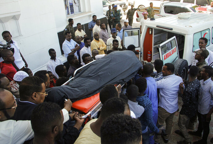 Mourners carry the body of Somali Canadian peace activist Almaas Elman to her funeral service in the capital Mogadishu, Somalia Friday, Nov. 22, 2019. Preliminary investigations show Almaas Elman was killed by a stray bullet inside a heavily defended base near the international airport earlier this week in Mogadishu, the peacekeeping mission in Somalia said Friday. (AP Photo/Farah Abdi Warsameh)