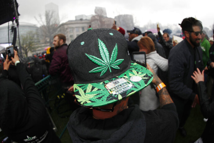 FILE - In this April 20, 2018 file photo, an attendee celebrates at 4:20 p.m. by lighting up marijuana during the Mile High 420 Festival in Denver. New research has found some Colorado teenagers who use marijuana are shifting away from smoking it in favor of edible products. About 78% of the Colorado high school students who reported consuming marijuana in 2017 said smoking was their usual method, down from 87% two years earlier. The number of teens who usually consumed edible marijuana products climbed to about 10% from 2% in the same two-year span while the number of users dabbing increased to about 7.5% from 4%. (AP Photo/David Zalubowski, File)