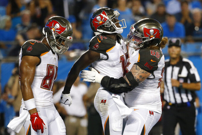 Tampa Bay Buccaneers center Ryan Jensen (66) and tight end O.J. Howard (80) celebrate with wide receiver Chris Godwin (12) following Godwin's touchdown against the Carolina Panthers during the first half of an NFL football game in Charlotte, N.C., Thursday, Sept. 12, 2019. (AP Photo/Brian Blanco)