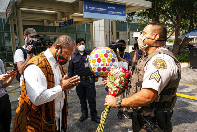 Najee Ali, of Project Islamic Hope, presents Sgt. Larry Villareal, of the Los Angeles County Sheriff Dept., flowers for deputies recovering at St. Francis Medical Center in Lynwood, Calif., Monday, Sept. 14, 2020. The two deputies were shot Saturday while in their patrol vehicle in an ambush-style attack. Ali was especially troubled by reports that protesters were at the hospital chanting