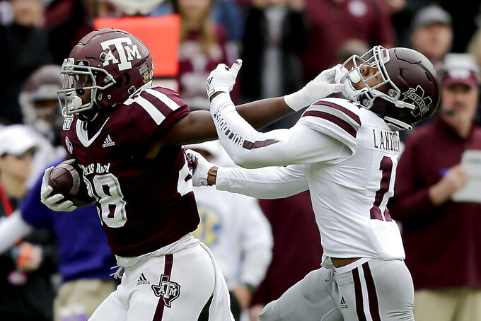 Texas A&M running back Isaiah Spiller (28) stiff arms Mississippi State safety Jaquarius Landrews (11) to avoid a tackle during the first quarter of an NCAA college football game, Saturday, Oct. 26, 2019, in College Station, Texas. (AP Photo/Sam Craft)