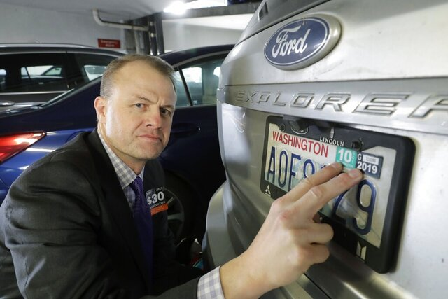 FILE - In this Nov. 26, 2019, file photo, Tim Eyman, a career anti-tax initiative promoter, poses for a photo with the expired car registration tabs on his SUV in a parking garage in Seattle. The Washington Supreme Court has unanimously struck down Eyman's Initiative 976, a measure that would have steeply discounted the price of car registrations while gutting transportation budgets across the state. The justices on Thursday, Oct. 15, 2020, said the measure violated the state Constitution's requirement that initiatives be limited to a single subject and said its description on the ballot was misleading. (AP Photo/Ted S. Warren, File)