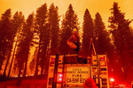 Firefighter Rosie Smith unloads hose from a truck while battling the Caldor Fire west of Strawberry in Eldorado National Forest, Calif., on Thursday, Aug. 26, 2021. (AP Photo/Noah Berger)
