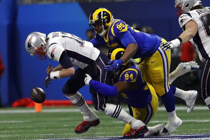New England Patriots' Tom Brady (12) fumbles the ball under pressure from Los Angeles Rams' John Franklin-Myers (94) and Ethan Westbrooks (95), during the first half of the NFL Super Bowl 53 football game Sunday, Feb. 3, 2019, in Atlanta. (AP Photo/Jeff Roberson)