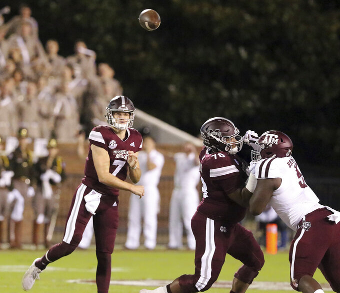 Mississippi State quarterback Nick Fitzgerald (7) throws a pass as offensive lineman Tyre Phillips (78) blocks Texas A&M defensive lineman Bobby Brown III (5) during the first half of an NCAA college football game on Saturday, Oct. 27, 2018, in Starkville, Miss. (AP Photo/Jim Lytle)