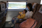A child plays with a smartphone on the knees of a woman during a high speed train from Henan to Beijing Wednesday, Sept. 15, 2021. China has set new rules limiting the amount of time kids can spend playing online games. (AP Photo/Ng Han Guan)