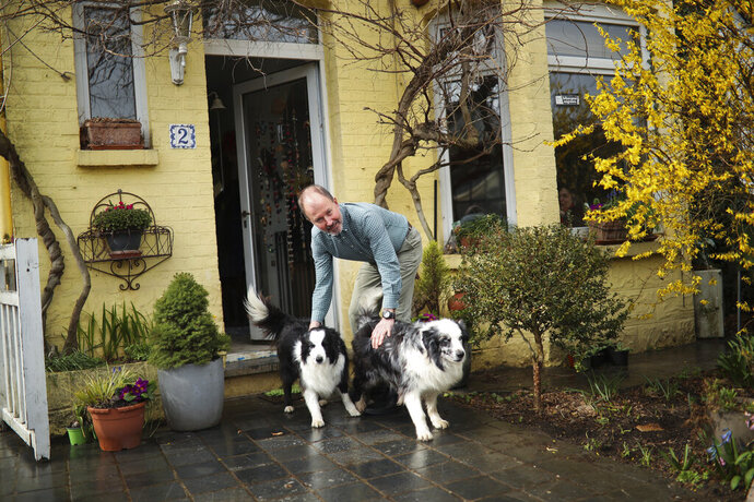 In this photo taken on Wednesday, March 13, 2019, British lobbyist Brian O'Riordan poses with his dogs in his house in Rixensart, outside Brussels. Britons in Brussels are fretting about how their country's looming departure will affect their daily lives. Growing numbers are taking Belgian nationality as a way of ensuring they can still live, work and travel freely in Europe after Brexit. (AP Photo/Francisco Seco)