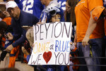 """FILE - An Indianapolis Colts fan holds a sign showing support for Denver Broncos quarterback Peyton Manning before an NFL football game between the Indianapolis Colts and the Broncos in Indianapolis, in this Sunday, Oct. 20, 2013, file photo. After five straight victories to open the season with his new team, the Broncos, Manning was on his way to his record fifth MVP award while setting all sorts of league passing marks. The matchup with the Colts in Indianapolis was ballyhooed like the second coming, but despite Manning's brilliance _ three touchdown passes, 386 yards in the air _ his replacement, Andrew Luck, got the win 39-33. """"I am kind of relieved in some ways that this game is over,"""" he said at the end of a long night.  (AP Photo/Michael Conroy, File)"""