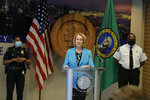 Seattle Mayor Jenny Durkan, center, speaks Monday, July 13, 2020, during a news conference at City Hall in Seattle as Police Chief Carmen Best, left, and Fire Chief Harold Scoggins , right, look on. Durkan and Best were critical of a plan backed by several city council members that seeks to cut the police department's budget by 50 percent. (AP Photo/Ted S. Warren)