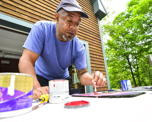 Bill Forchion, of Brattleboro, Vt., paints hearts onto slate and gives them out for free to people in the community in hopes of raising their spirits Thursday, May 28, 2020, during the COVID-19 pandemic. (Kristopher Radder/The Brattleboro Reformer via AP)