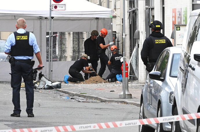 Danish police technicians inspect the scene outside of a local police station in Copenhagen, Saturday, Aug. 10, 2019, after it was hit by an explosion early morning, causing damage but no injuries.  This follows-on from Tuesday's explosion which occurred outside the Danish Tax Agency's office in Copenhagen. (Philip Davali/Ritzau Scanpix via AP)