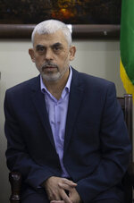 Yahya Sinwar, the Hamas militant group's leader in the Gaza Strip, meets with the head of the Central Elections Commission, Hanna Nasser, in Gaza City, Monday, Oct. 28, 2019. The militant Hamas group that runs the Gaza Strip says it's ready to go for Palestinian elections. (AP Photo/Khalil Hamra)