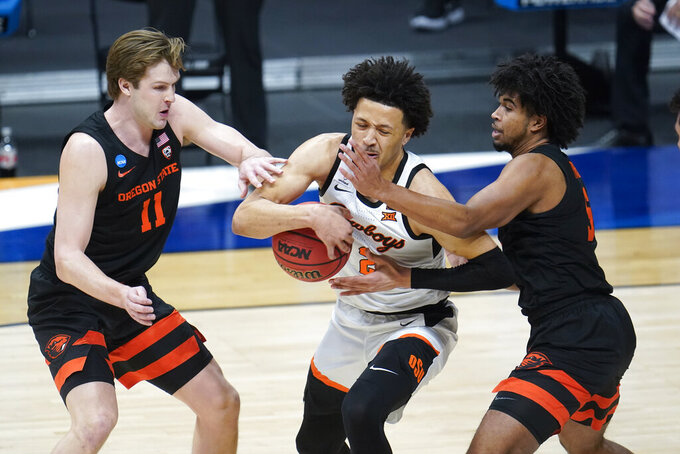 Oklahoma State guard Cade Cunningham (2) drives between Oregon State guard Zach Reichle (11) and Ethan Thompson (5) during the first half of a men's college basketball game in the second round of the NCAA tournament at Hinkle Fieldhouse in Indianapolis, Sunday, March 21, 2021. (AP Photo/Paul Sancya)