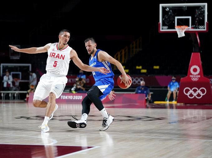 Czech Republic's Jakub Sirina, right, drives the ball around Iran's Pujan Jalalpoor during men's basketball game at the 2020 Summer Olympics, Sunday, July 25, 2021, in Saitama, Japan. (AP Photo/Charlie Neibergall)