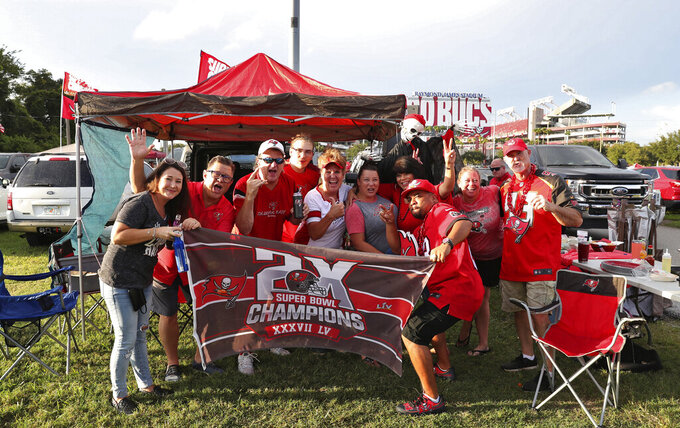 Tampa Bay Buccaneers fans tailgate outside Raymond James Stadium before an NFL football game against the Dallas Cowboys Thursday, Sept. 9, 2021, in Tampa, Fla. (AP Photo/Mark LoMoglio)