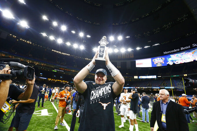 Texas quarterback Sam Ehlinger holds up his MVP trophy after Texas defeated Georgia 28-21 in the Sugar Bowl NCAA college football game in New Orleans, Tuesday, Jan. 1, 2019. (AP Photo/Butch Dill)