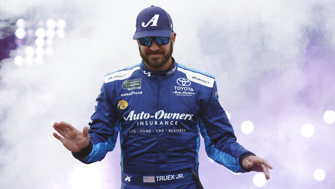 Martin Truex Jr., waves to fans during driver introductions prior to the start of the NASCAR Cup series auto race at Richmond Raceway in Richmond, Va., Saturday, April 13, 2019. (AP Photo/Steve Helber)