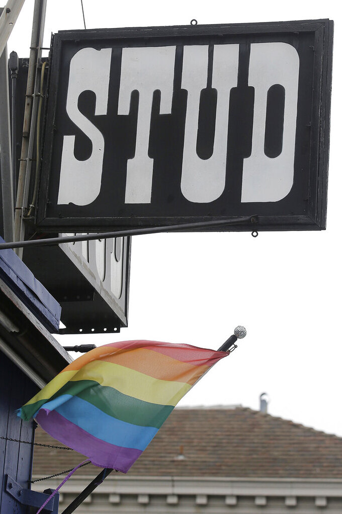 FILE - This July 6, 2016, file photo shows a rainbow flag flying under a sign for The Stud bar in San Francisco. The Stud, one of the nation's most celebrated gay bars, is being forced from its home amid the financial fallout of the coronavirus pandemic. (AP Photo/Jeff Chiu, File)