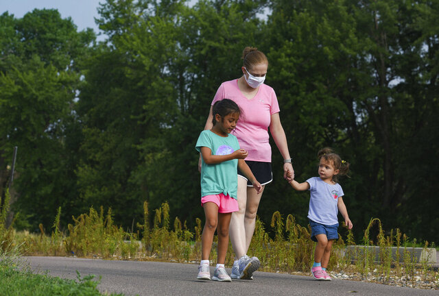 Mollie Sanchez goes for a walk with her daughters, Liliana (6) and Zoie (2) on Wednesday, July 29, 2020 at Yankton Trail Park in Sioux Falls, S.D. Sanchez won the mayor's fitness challenge to bike, walk or run 100 miles in 100 days. (Erin Bormett /The Argus Leader via AP)