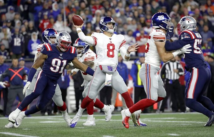 New York Giants quarterback Daniel Jones passes under pressure from New England Patriots defensive end Deatrich Wise, left, and linebacker Kyle Van Noy, right, in the first half of an NFL football game, Thursday, Oct. 10, 2019, in Foxborough, Mass. (AP Photo/Elise Amendola)