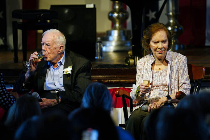 Former President Jimmy Carter sips champagne as his wife former first lady Rosalynn Carter speaks during a reception to celebrate their 75th wedding anniversary Saturday, July 10, 2021, in Plains, Ga.. (AP Photo/John Bazemore, Pool)