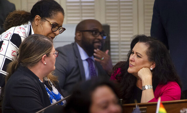 Assemblywoman Lorena Gonzalez, D-San Diego, talks with other assembly members on the Assembly floor at the Capitol in Sacramento, Calif., on Thursday, Feb. 27, 2020. Gonzalez has proposed an amendment to Assembly Bill 5 — which requires many independent contractors to be re-classified as employees with benefits — that removes the submission cap but also mandates that freelancers cannot replace regular employees. (Daniel Kim/The Sacramento Bee via AP)