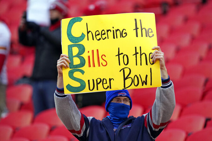 A fan watches players warm up before the AFC championship NFL football game between the Kansas City Chiefs and the Buffalo Bills, Sunday, Jan. 24, 2021, in Kansas City, Mo. (AP Photo/Orlin Wagner)