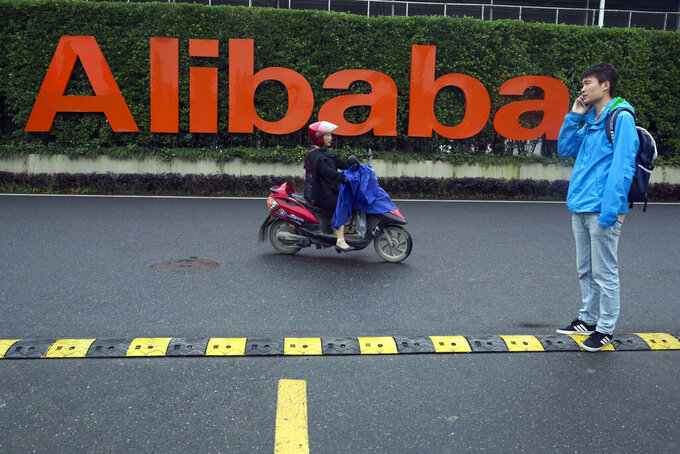 FILE - In this May 27, 2016, file photo, a man talks on his phone as a woman rides on an electric bike past a company logo at the Alibaba Group headquarters in Hangzhou in eastern China's Zhejiang province. China's largest e-commerce company Alibaba said Monday, Aug. 9, 2021, that it fired the manager accused of sexual misconduct and pledged to strengthen its anti-sexual harassment policy after the female employee at the company accused the firm of suppressing her report of sexual assault. (AP Photo/Ng Han Guan, File)