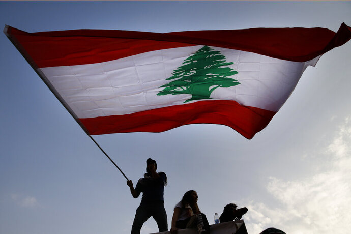A protester waves the Lebanese flag during ongoing protests against the government, in front of the government palace in Beirut, Lebanon, Saturday, Nov. 9, 2019. Lebanon's president is meeting with several Cabinet ministers and top banking officials in search for solutions for the deepening financial and economic crisis. (AP Photo/Bilal Hussein)
