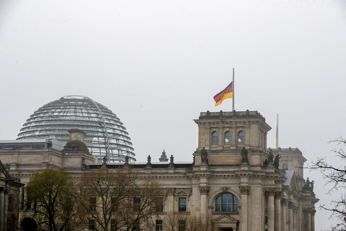 The German flag on top of the Reichstag building is seen at half-mast on the occasion of the central memorial for those who died in the Corona pandemic in Germany, Berlin, April 18, 2021. (Christoph Soeder/dpa via AP)