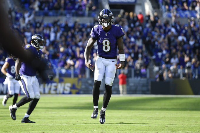 Baltimore Ravens quarterback Lamar Jackson reacts after throwing a touchdown pass to wide receiver Marquise Brown, not visible, during the second half of an NFL football game against the Cincinnati Bengals, Sunday, Oct. 24, 2021, in Baltimore. (AP Photo/Nick Wass)